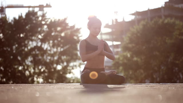 Young woman doing yoga moditating on a rooftop at sunset video