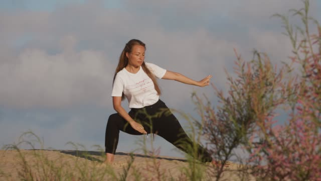young woman doing yoga on in beautiful asana in front of dune landscape with blue sky, early morning meditation - active lifestyle stock videos & royalty-free footage