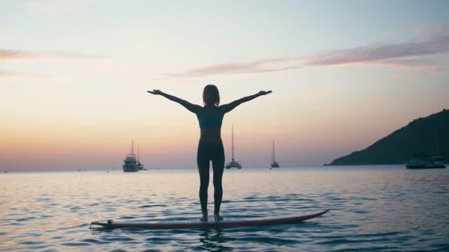молодая женщина делает йогу на sup борту с веслом на закате - mindfulness стоковые видео и кадры b-roll