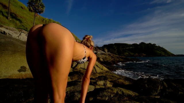 Young woman doing yoga on the rock near the sea. Young woman doing yoga on the rock near the sea. yoga stock videos & royalty-free footage