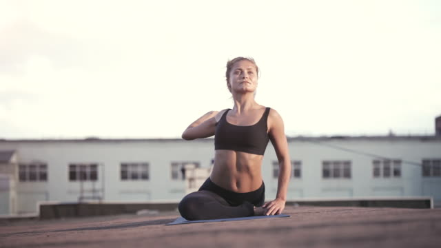 Young woman doing yoga outdoors on a rooftop at sunset Young woman doing yoga meditating outdoors on a rooftop at sunset lotus position stock videos & royalty-free footage