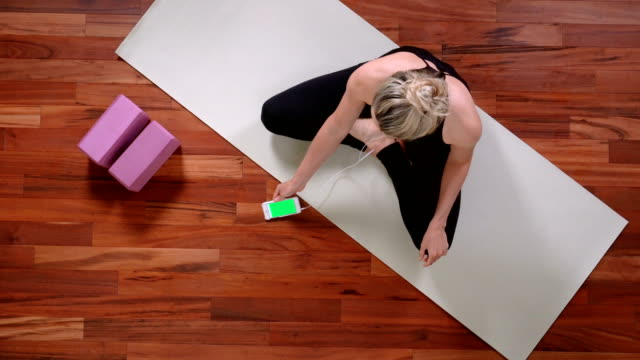 young woman doing yoga with smart phone - exercise equipment stock videos & royalty-free footage