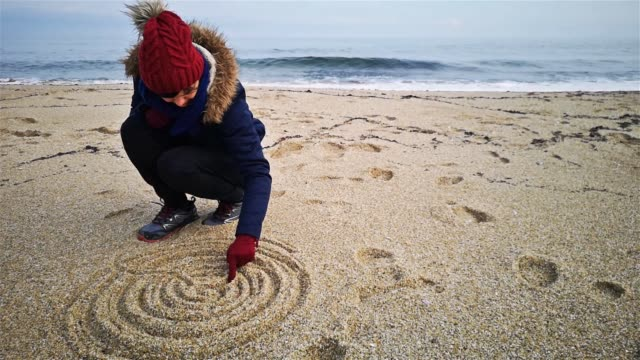 vídeos de stock e filmes b-roll de young woman drawing mandala on sand at beach shore - mandala