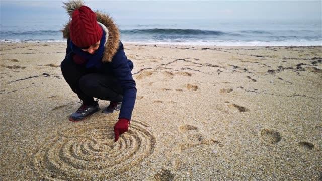 stockvideo's en b-roll-footage met jonge vrouw tekening mandala op zand op beach shore - mandala