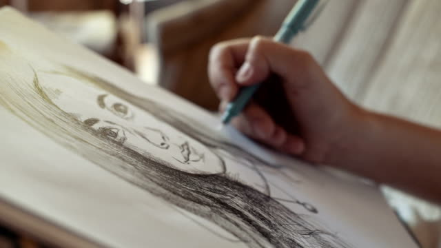 Young woman drawing the portrait in cafe, close up video