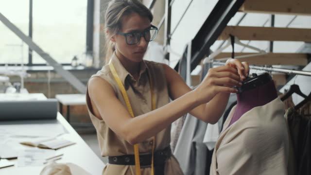 junge frau dressing mannequin mit stoff in schneiderei studio - kurzwaren stock-videos und b-roll-filmmaterial