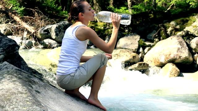 Junge Frau drinkig Wasser vom Fluss in den Bergen – Video