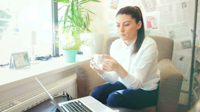 Young woman drinking a cup of tea while using laptop. video