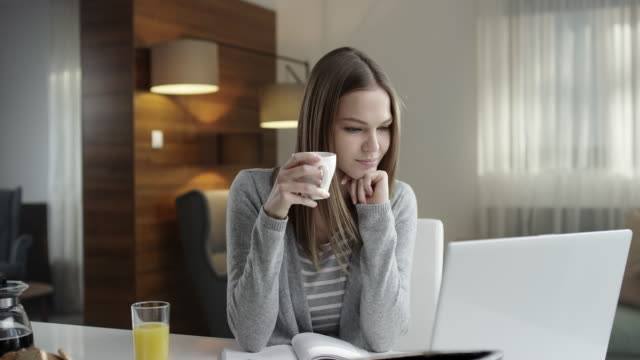 Young woman drinking coffee and using laptop video