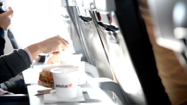 Young woman drinking coffee on an airplane , slow motion video