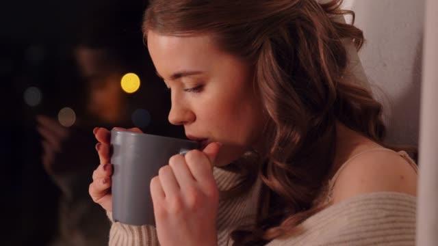 ung kvinna dricker kaffe eller te vid fönstret video