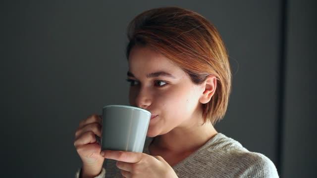 vídeos y material grabado en eventos de stock de mujer joven bebiendo café - café bebida
