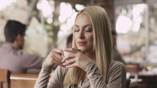 giovane donna bere il caffè - annusare video stock e b–roll
