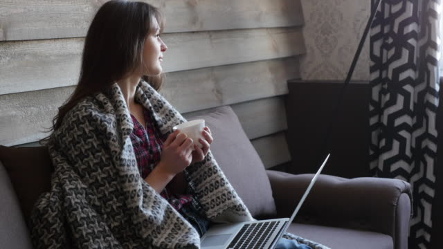 young woman drinking from a cup and using a laptop video