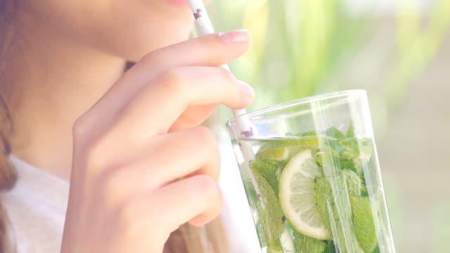 young woman drinking lime and mint detox water. - disintossicazione video stock e b–roll