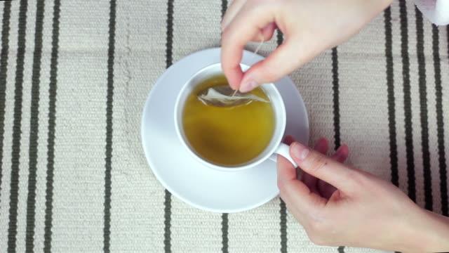 vídeos y material grabado en eventos de stock de mujer joven bebiendo té acercamiento. - manzanilla