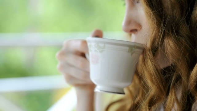 Young woman drinking tea video