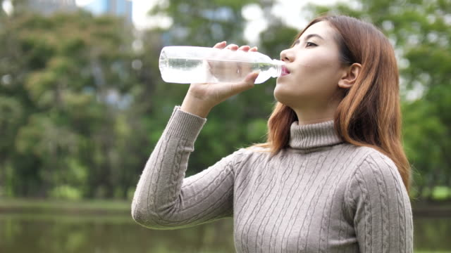 Young woman drinking water after fitness exercise video