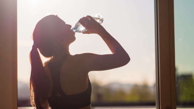 Young woman drinking water after high intensity training video