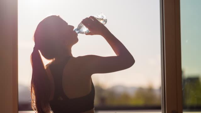 giovane donna acqua potabile dopo allenamento fitness - acqua potabile video stock e b–roll