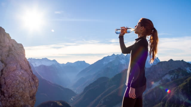 Young woman drinking water at the top of a mountain video