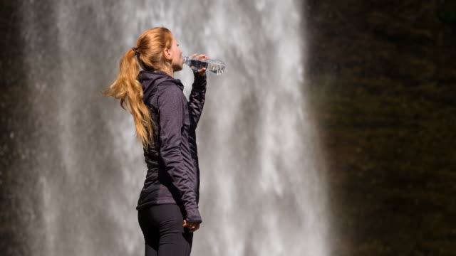 Young woman drinking water in front of a waterfall video