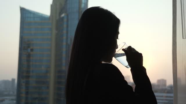 ung kvinna dricksvatten i hennes rum. - mineral bildbanksvideor och videomaterial från bakom kulisserna