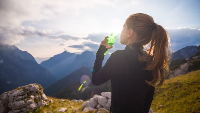Young woman drinking water in the mountains video