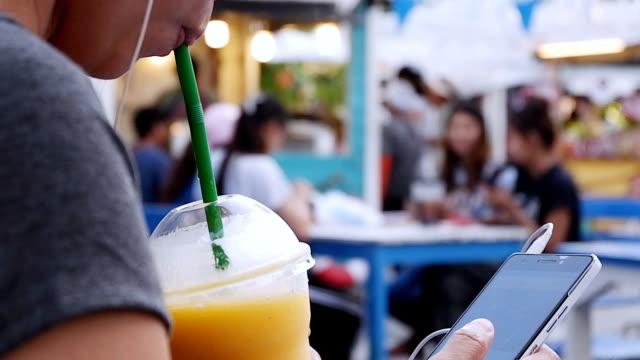 Junge Frau trinken gelbe Mango Smoothie am Strand. Nahaufnahme der weiblichen genießen Sommerferien. Sie lebt gesunden Lebensstil im freien Lächeln auf den Lippen. – Video