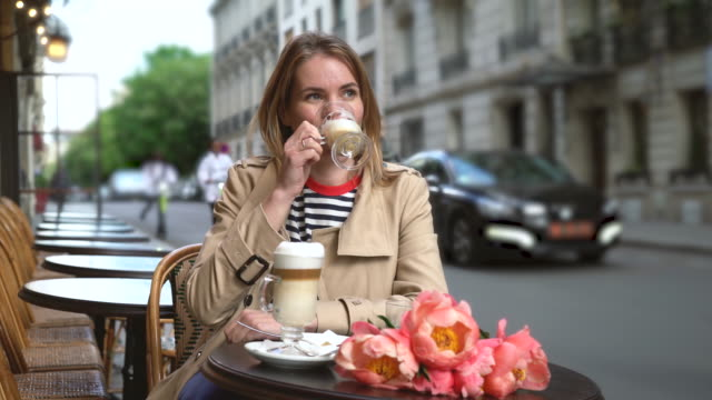 Young woman drinks coffee in a street cafe