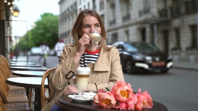 vídeos y material grabado en eventos de stock de jovencita bebe café en un café callejero - francia