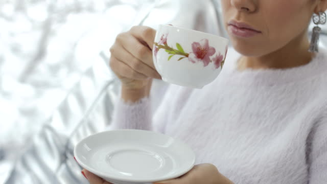 Young woman drinks tea video