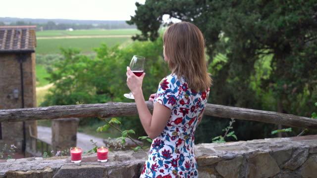genç kadın kırsal villada şarap içer - toskana stok videoları ve detay görüntü çekimi