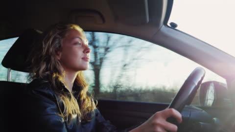 vídeos y material grabado en eventos de stock de jovencita conduciendo un suv. paseos por el campo en un camino desigual en los rayos de la puesta de sol - conducir