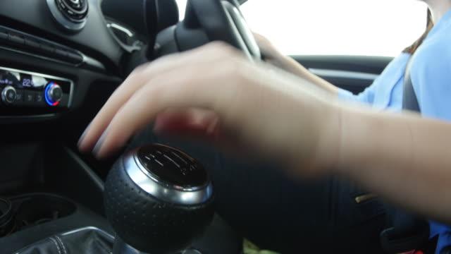 young woman driving in a car, gear change close-up - växelspak bildbanksvideor och videomaterial från bakom kulisserna