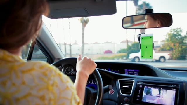 vídeos de stock, filmes e b-roll de jovem mulher dirigindo com celular tela verde - dividindo carro