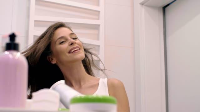 young woman drying her hair in bathroom - prendersi cura del corpo video stock e b–roll