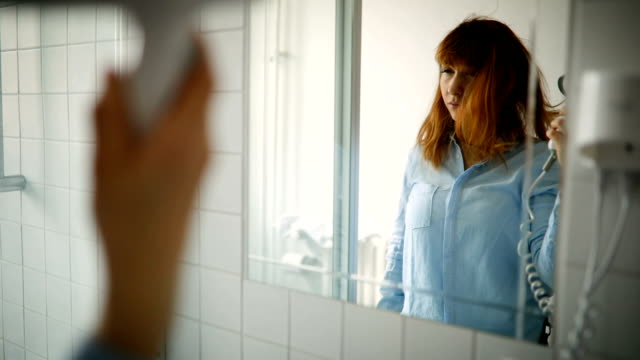 Young Woman Drying Her Hair in Bathroom Young Woman Drying Her Red Hair in Bathroom in a front of Mirror redhead stock videos & royalty-free footage
