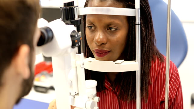 Young woman during an eyesight exam Beautiful young woman at ophthalmologist , Eyesight exam ophthalmologist stock videos & royalty-free footage