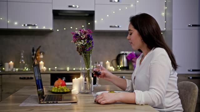 młoda kobieta podczas randki online w domu. widok z boku młodej kobiety pijącej wino i uśmiechniętej siedzącej przy stole i nawiązującej rozmowy wideo z chłopakiem podczas romantycznej kolacji w kuchni w domu - data filmów i materiałów b-roll