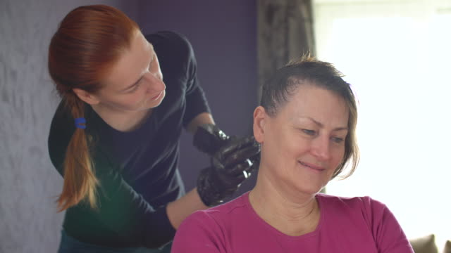 junge frau färbt senior frau haare mit haarfärbemittel - haartönung stock-videos und b-roll-filmmaterial
