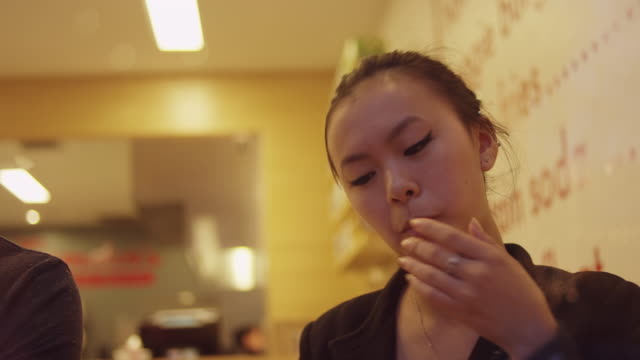 A young woman eating a burger at a restaurant, through the window video