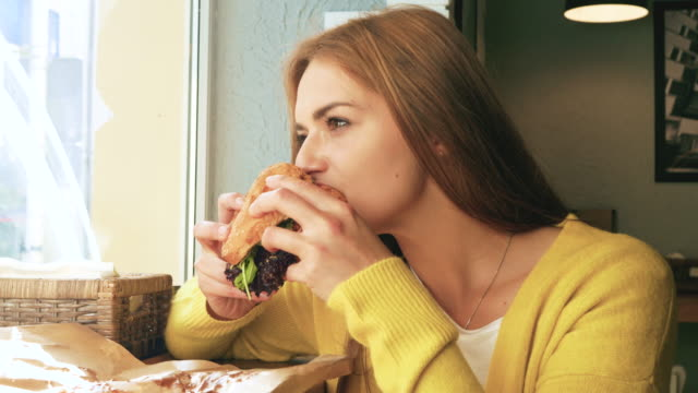 young woman eating a hamburger - cheeseburger filmów i materiałów b-roll