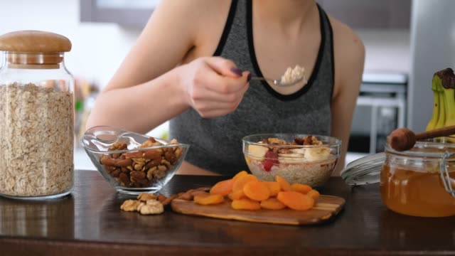 young woman eating a healthy oatmeal after a workout. - noci video stock e b–roll