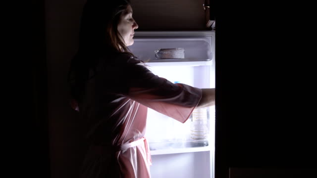 Young woman eating at night near the refrigerator