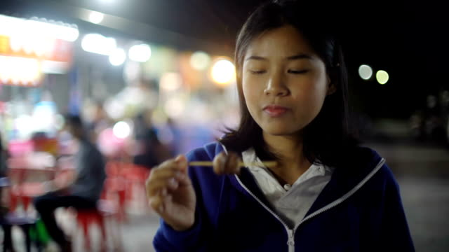 Young woman eating barbeque on skewers in night food market video