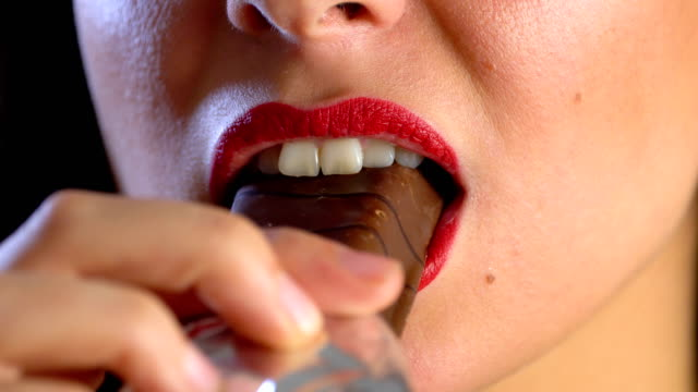young woman eating chocolate cake - cioccolato video stock e b–roll