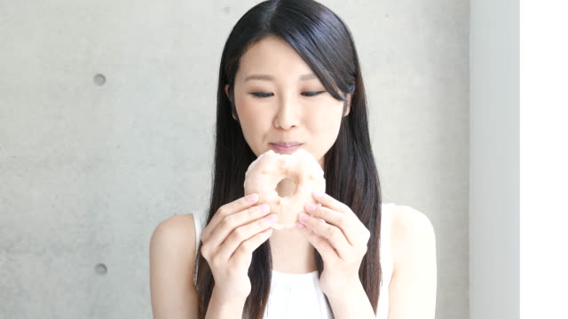 young woman eating donut - bombolone video stock e b–roll