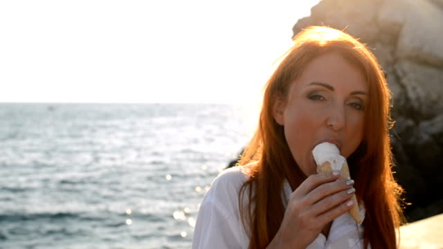 Young woman eating ice cream on the seashore video