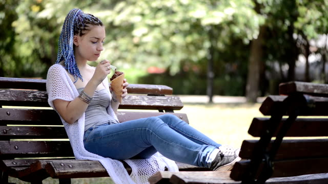 Young woman eating ice cream sitting on a bench in the park
